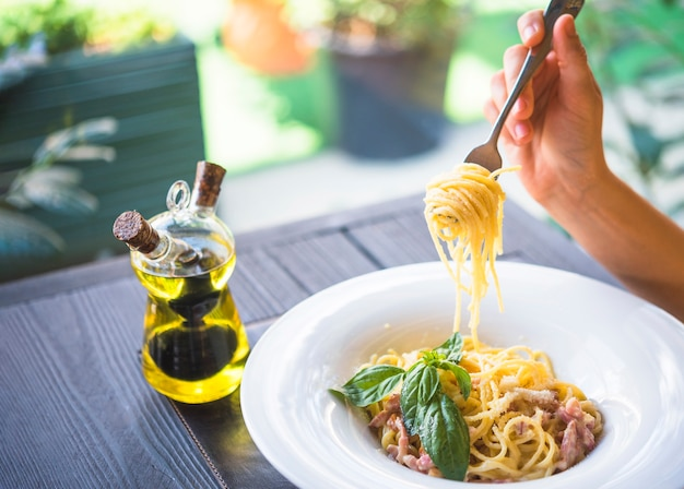 Botella de aceite de oliva con una persona con espaguetis con un tenedor.