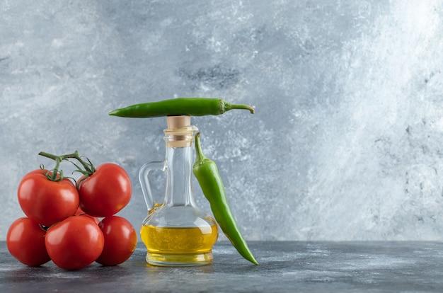 Botella de aceite de oliva, pimientos verdes y tomates sobre fondo de mármol