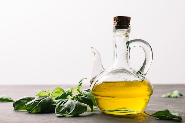 Botella de aceite de oliva que refleja la luz con espinacas alrededor