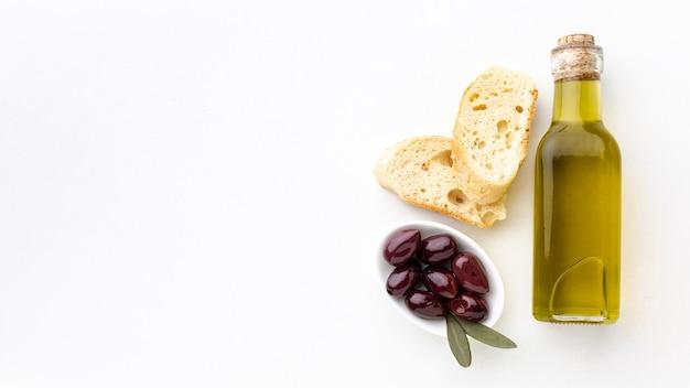 Botella de aceite de oliva rebanadas de pan y aceitunas moradas con espacio de copia