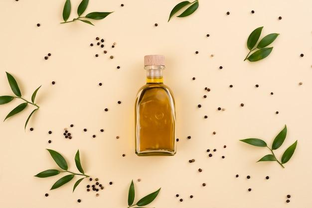 Botella de aceite de oliva rodeada de hojas de olivo