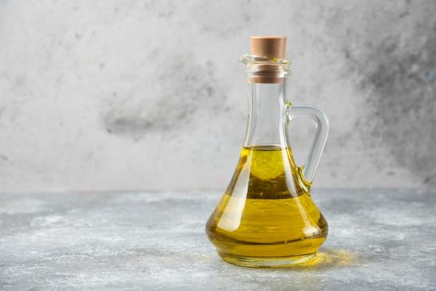 Botella de aceite de oliva sobre mesa de mármol.