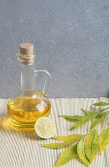 Una botella de aceite con una rodaja de limón sobre fondo gris