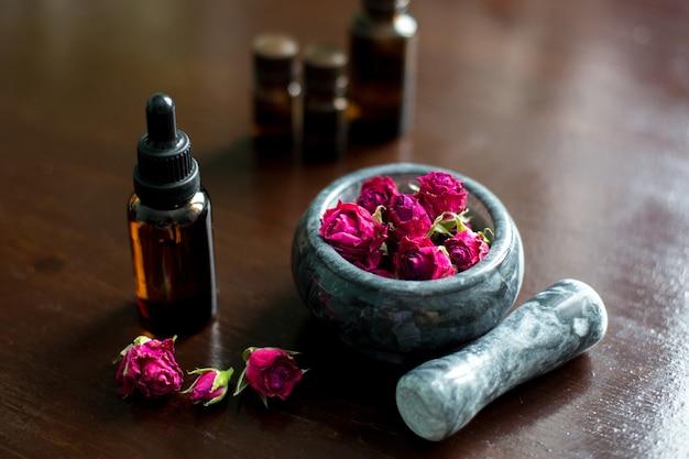 Una botella de aceite de rosa y flores.