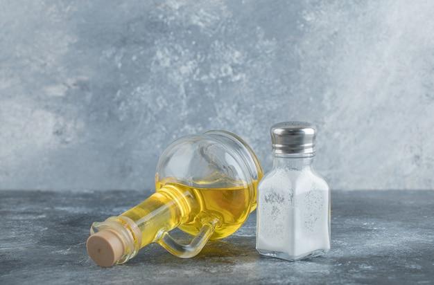 Botella de aceite y sal sobre fondo gris