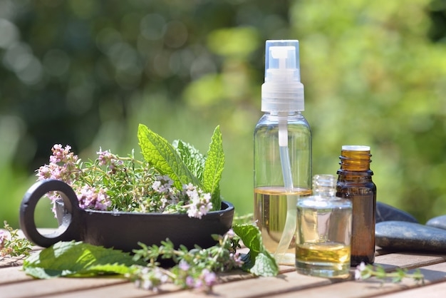 Botella de aceites esenciales derramada sobre una mesa con flores de lavanda sobre fondo verde bokeh