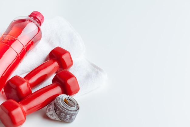 Botella de agua y aparatos de gimnasia aislados en blanco