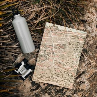 Botella de agua; binoculares y mapa en roca cerca de la hierba