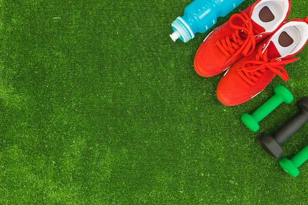 Botella de agua; calzado deportivo rojo y mancuernas en césped verde