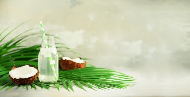 Botella de agua de coco y frutas maduras frescas. concepto de comida de verano vegetariana, vegana, bebida detox. jugo de coco con paja sobre hojas de palma.