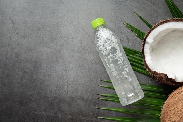 Botella de agua de coco sobre fondo oscuro
