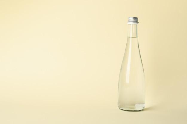 Botella con agua en color beige, espacio para texto