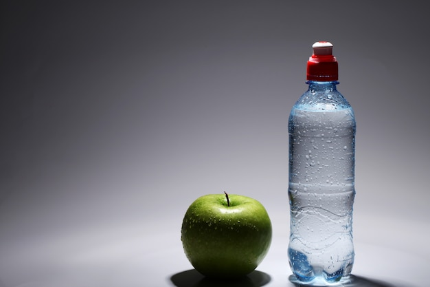 Botella de agua fría fresca y manzana verde