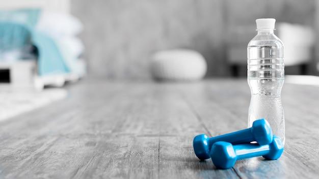 Botella de agua junto a pesas