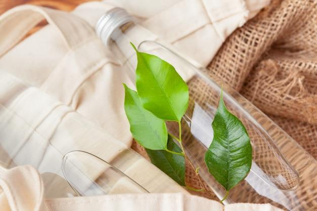 Botella con agua limpia y las hojas verdes.