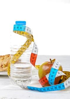 Botella de agua y manzana con cinta métrica