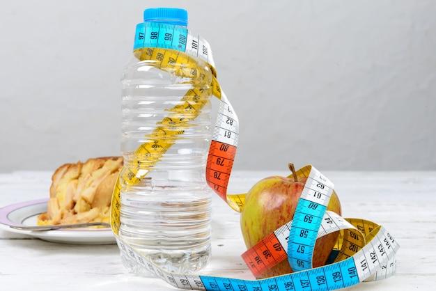 Botella de agua y una manzana con una cinta métrica.