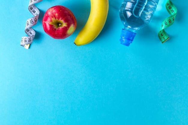 Una botella de agua, una manzana, un plátano y una cinta métrica. concepto de deporte y dieta. deporte y estilo de vida saludable. fondo copyspace