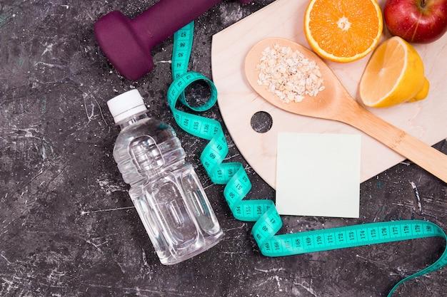 Botella de agua, pesas, cinta métrica, comida dietética sobre una superficie negra
