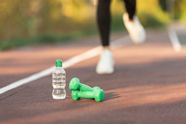 Botella de agua y pesas verdes.