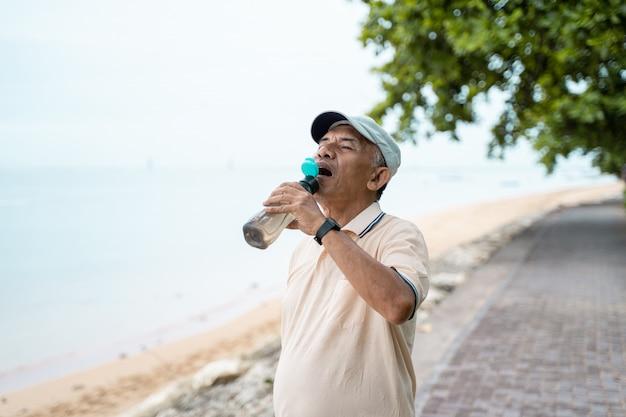 Botella de agua potable asiática masculina senior