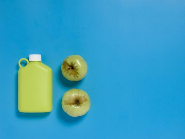 Botella de agua reutilizable verde con manzanas verdes feas en mesa azul.