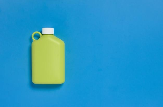 Botella de agua reutilizable verde en mesa azul.