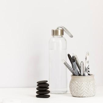 Botella de agua con surtido de bolígrafos y piedra de masaje.