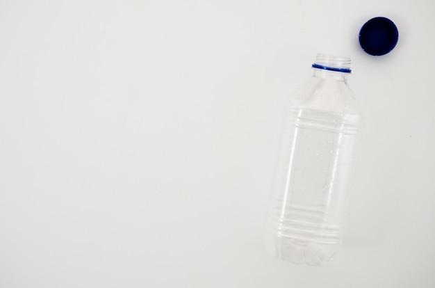 Botella de agua transparente vacía con su tapa aislada sobre fondo blanco.