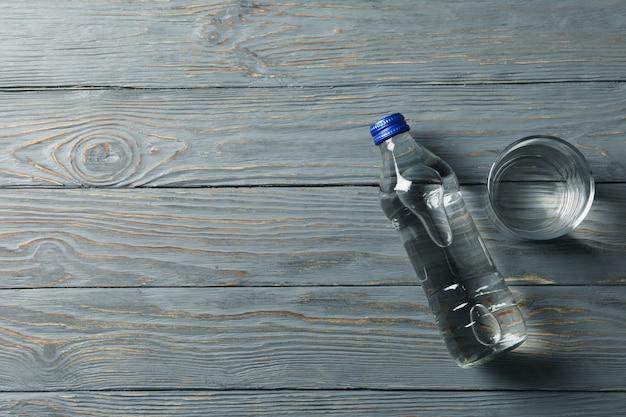Botella con agua y vaso sobre madera, espacio para texto