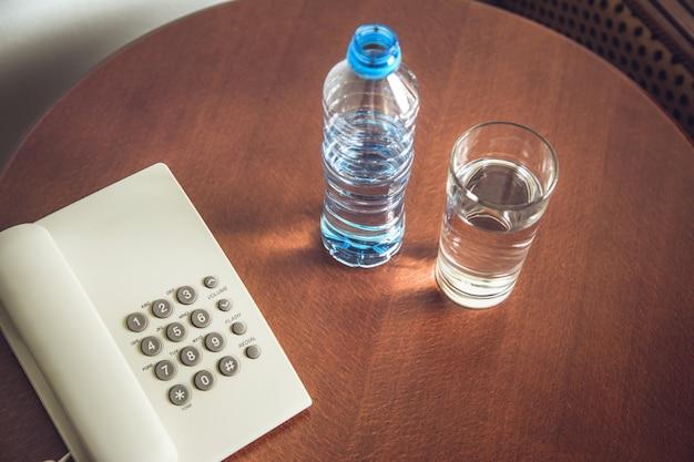 Botella de agua y vaso con teléfono en la mesa