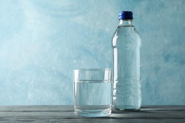 Botella con agua y vidrio en mesa de madera, espacio para texto