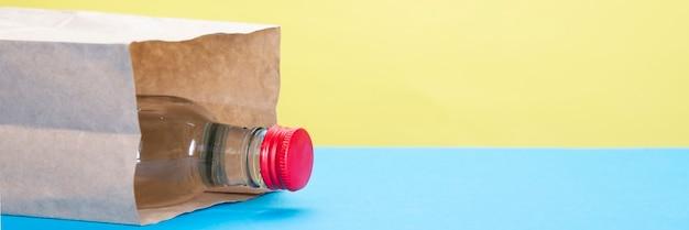 Botella de alcohol con corcho rojo en bolsa de papel sobre fondo amarillo y azul.