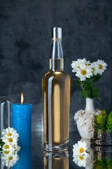 Botella de alcohol con flores y velas.