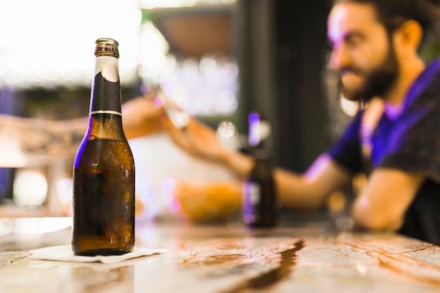 Botella de alcohol en papel de seda sobre la mesa de madera