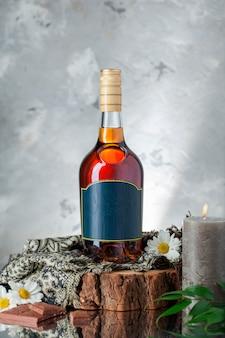 Botella de alcohol con planta, bufanda, margaritas y velas. Foto gratis