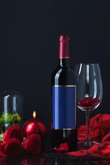 Botella de alcohol con rosas, copa, vela y bufanda.
