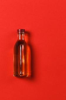 Botella con alcohol sobre fondo rojo.