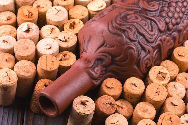 Botella de arcilla de vino y corcho en una mesa de madera oscura.