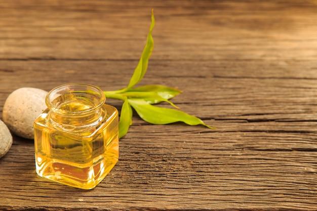 Botella de aroma de aceite esencial o spa y hojas verdes naturales en mesa de madera