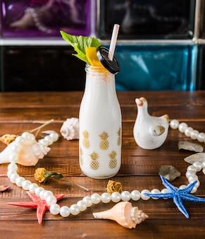 Botella de batido lechoso con pipa y decoraciones de playa.