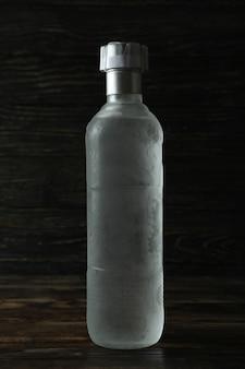 Botella de bebida en blanco en la pared de madera