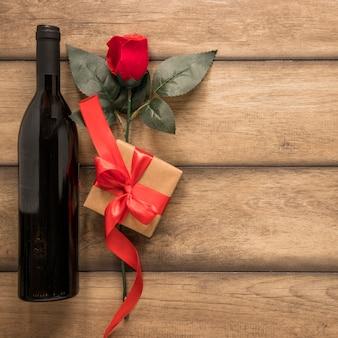 Botella de bebida cerca del presente y flor.