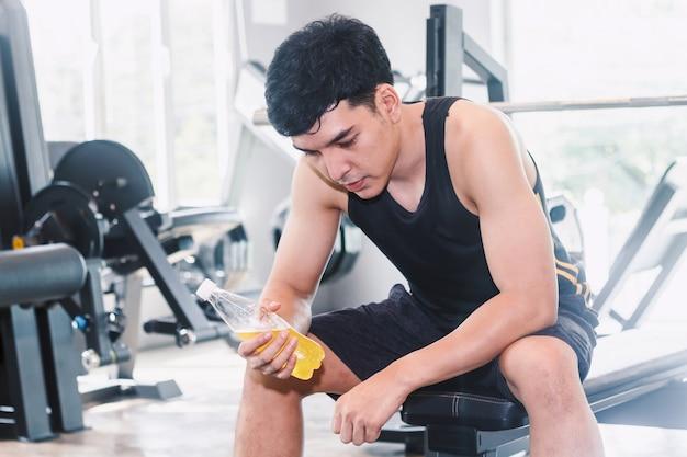 Botella de la bebida de la energía del holdind del hombre del deporte en el concepto del gymfitness y del estilo de vida