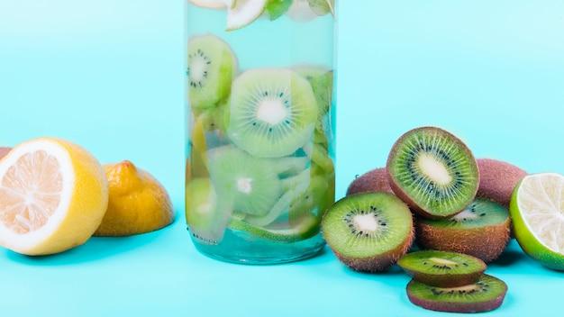 Botella de bebida con kiwi y limón.