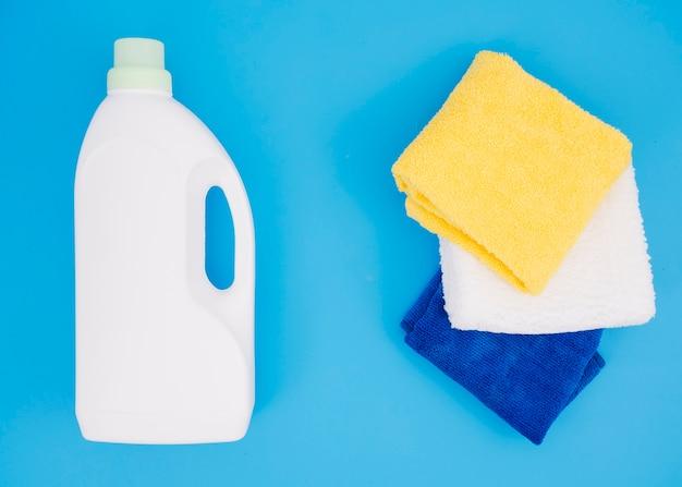 Botella blanca de detergente cerca de la servilleta de varios colores sobre fondo azul