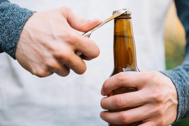 Botella de cerveza de apertura de mano de una persona con el abrelatas