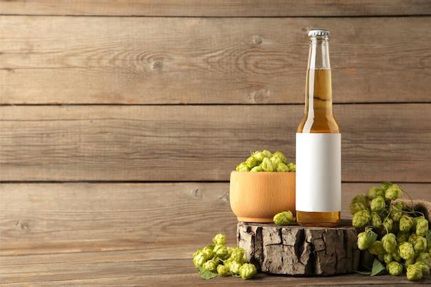 Botella de cerveza con conos de lúpulo sobre fondo gris con espacio de copia, de cerca.
