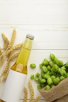 Botella de cerveza con conos de lúpulo y trigo sobre fondo blanco, de cerca.