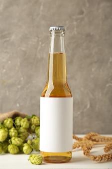 Botella de cerveza con conos de lúpulo y trigo sobre fondo gris, de cerca. vista superior
